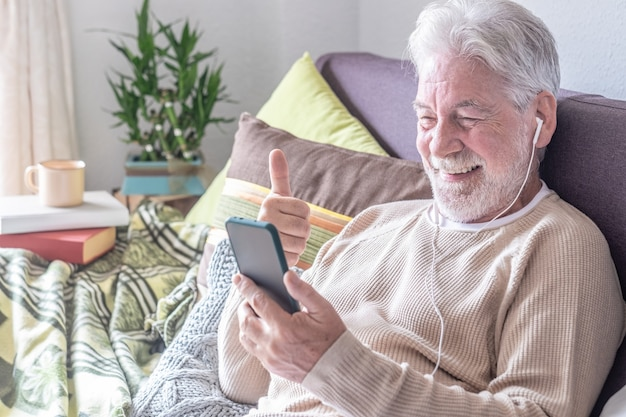 Smiling senior man, white hair, sitting on sofa at home in video call with mobile phone, thumb up for positive message