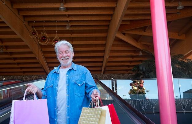 モールでクリスマスの買い物を楽しんでいる白い髪の年配の男性の笑顔