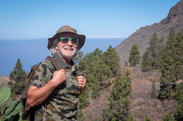 모자와 배낭을 메고 테네리페 섬의 산맥에서 여행을 즐기는 웃고 있는 노인 - 활동적인 노인들을 위한 여름 휴가 개념