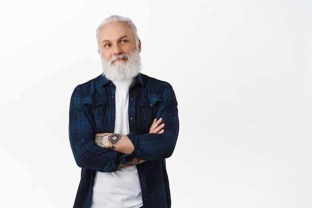 Sorridente uomo anziano con tatuaggi che guarda da parte il logo promozionale, incrocia le braccia sul petto e pensa, prende una decisione, contempla qualcosa sul lato destro, in piedi sul muro bianco
