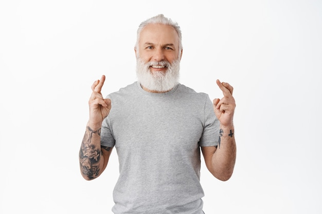 Smiling senior man with tattoos making wish, looking optimistic and hopeful, waiting for good news, dream come true, standing in casual t-shirt against white wall