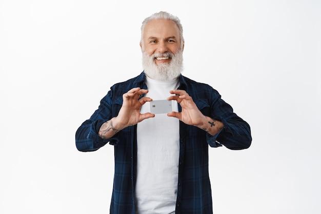 Sorridente uomo anziano con tatuaggi che mostra la carta di credito, raccomandando la sua banca, soddisfatto del servizio, in piedi sul muro bianco