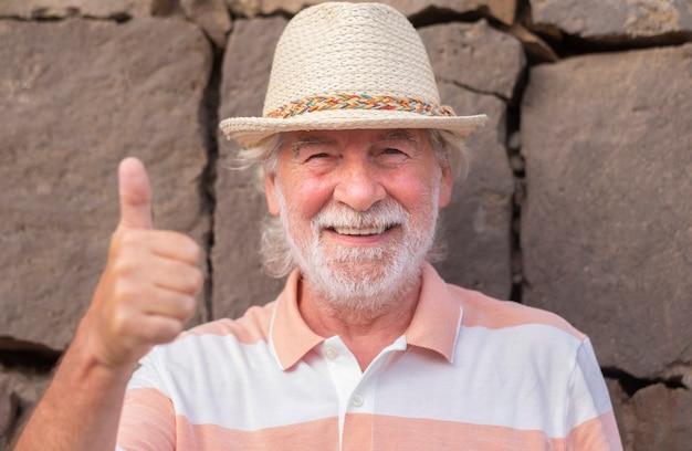 흰 머리와 밀짚 모자를 쓴 웃고 있는 노인이 야외에 서서 손으로 확인 표시를 하고 있다