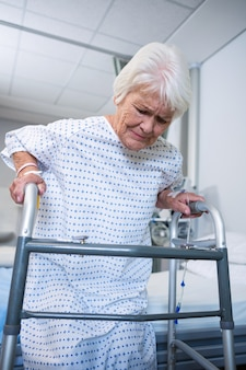 起床するウォーキングフレームを保持している上級の患者の笑顔