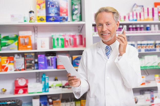 Smiling senior phoning while reading prescription
