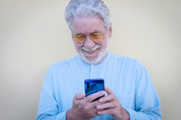 Улыбающийся старший седой мужчина, использующий мобильный телефон в видео-звонке, эти люди, пользующиеся технологиями