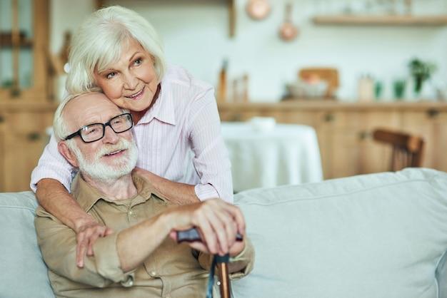 Smiling senior wife hugging her husband at home
