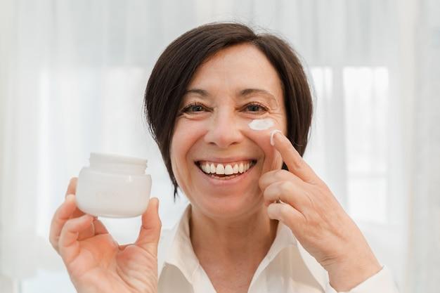 自宅でアンチエイジングフェイスクリームを適用する笑顔の年配の女性。日保湿剤を使用して幸せな成熟した女性