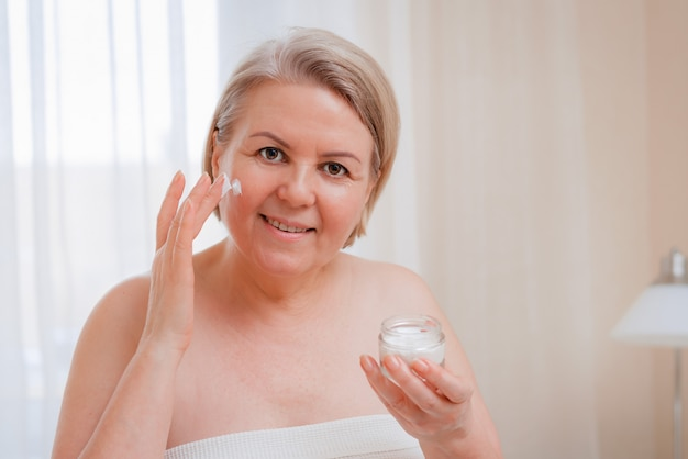 Smiling senior woman applying anti-aging lotion to remove dark circles under eyes.