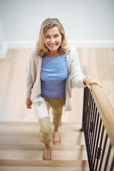 Smiling senior woman climbing upstairs at home