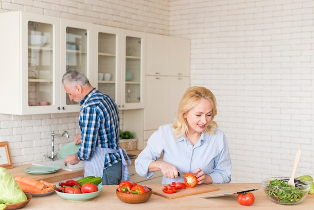Smiling senior woman cutting the red bell pepper with knife looking at digital tablet and his husband washing dishes in kitchen sink