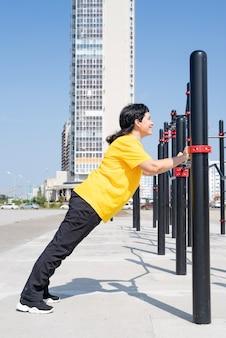 Улыбающаяся старшая женщина делает отжимания на открытом воздухе на барах спортивной площадки