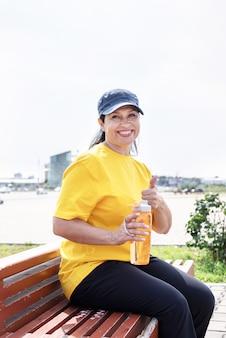 Улыбающаяся старшая женщина пьет воду после тренировки на открытом воздухе на спортивной площадке, показывает палец вверх