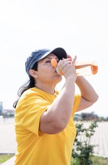 Улыбающаяся старшая женщина пьет воду после тренировки на открытом воздухе на спортивной площадке