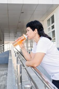 都会のシーンで屋外トレーニング後の水を飲む年配の女性の笑顔