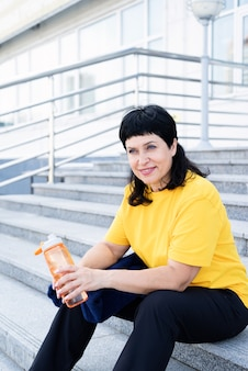Smiling senior woman drinking water after workout outdoors on urban scene