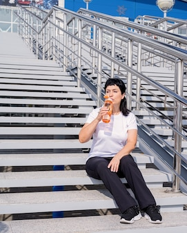 Smiling senior woman drinking water after workout outdoors
