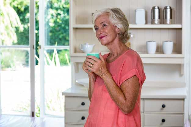 Smiling senior woman having coffee in kitchen