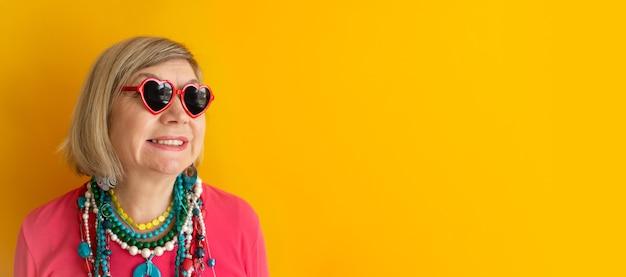 세련된 옷과 안경을 쓰고 웃고 있는 노인 여성은 노인에 대한 하트 개념을 가지고 있습니다.