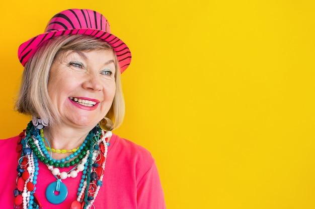 세련된 옷과 안경 하트 컨셉으로 즐겁게 웃고 있는 노인 여성