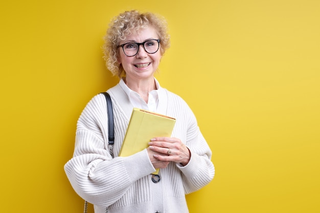 Smiling senior woman holding book in hands, wearing eyeglasses, confident teacher ready to teach you, experienced tutor posing isolated