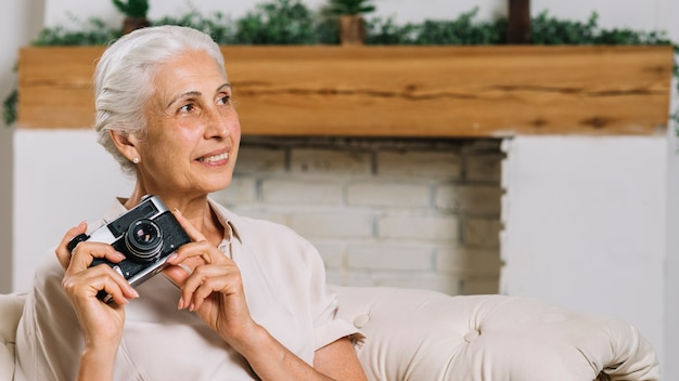 Smiling senior woman holding camera in hand looking away