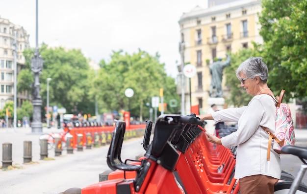 公園で電動自転車を借りて携帯電話を持っている笑顔の年配の女性。自由とスポーツを楽しむ幸せなカジュアル退職者