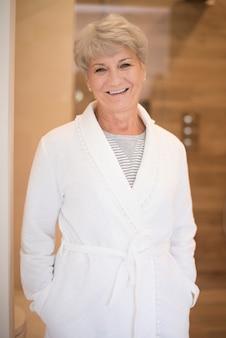 バスローブで笑顔の年配の女性
