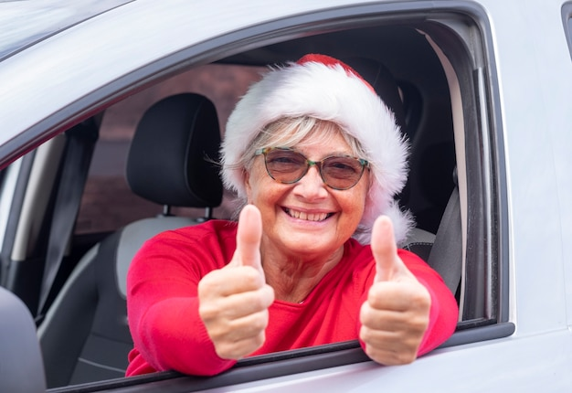 Smiling senior woman inside the car wearing a christmas hat smiling with thumbs up out the window waiting for the upcoming holiday - event. concept of happiness