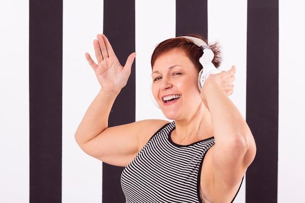 Smiling senior woman listening music