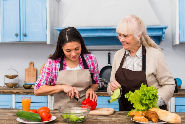 Smiling senior woman looking at daughter cutting vegetable in the kitchen