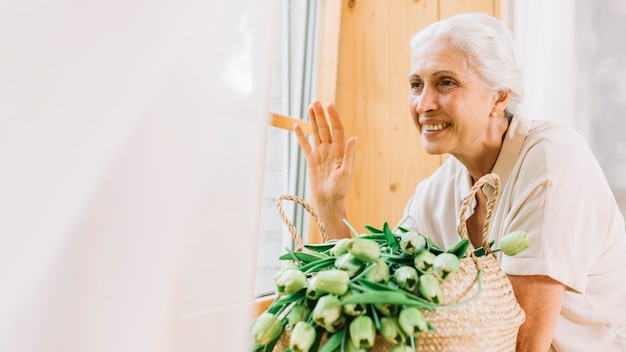 Smiling senior woman looking through window waving her hand