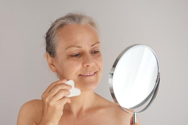 거울을 보면서 옥 판자로 그녀의 얼굴을 마사지 하는 웃는 수석 여자