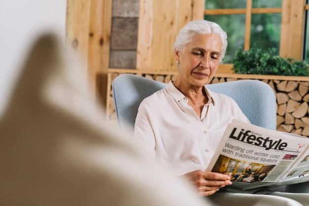 Smiling senior woman reading newspaper at home