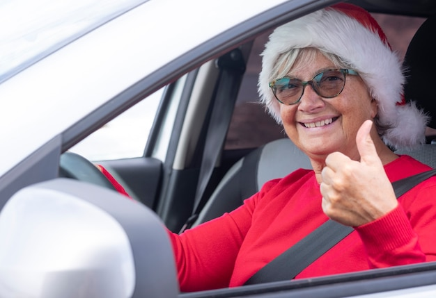 Smiling senior woman red dressed wearing a christmas hat smiles driving the car looking at camera with thumbs up.