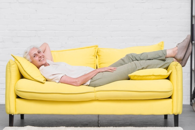 Smiling senior woman relaxing on yellow sofa at home