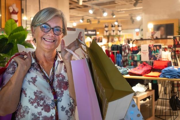 ショッピングバッグが満載のモールでの購入に満足している笑顔の年配の女性