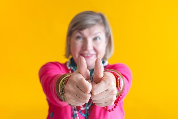세련된 옷을 입고 즐거운 시간을 보내는 손으로 클래스 기호를 보여주는 웃는 고위 여성