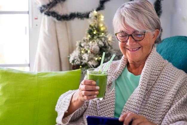 家に座って、彼女のスマートフォンを見ながら緑のスムージーのガラスを保持している笑顔の年配の女性。果物と野菜を使った健康的なデトックスビーガン食。背景のクリスマスの装飾
