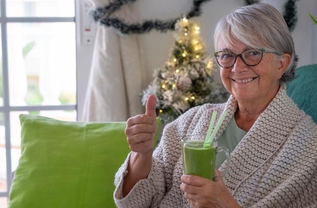 家に座って、自家製の緑のスムージードリンクを持って笑顔の年配の女性。野菜や果物を使ったヘルシーなデトックスビーガンダイエット。背景のクリスマスの装飾