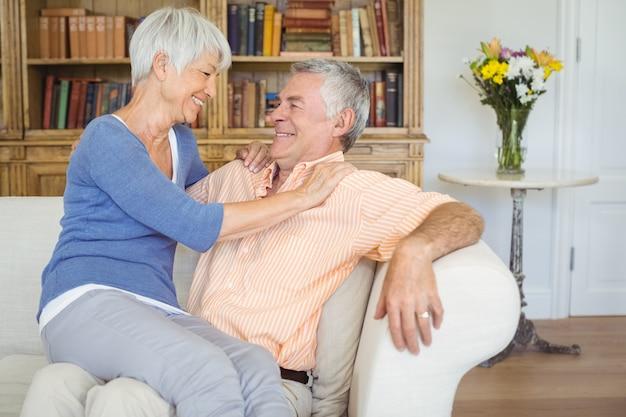 リビングルームでひざの上に座っている笑顔の年配の女性