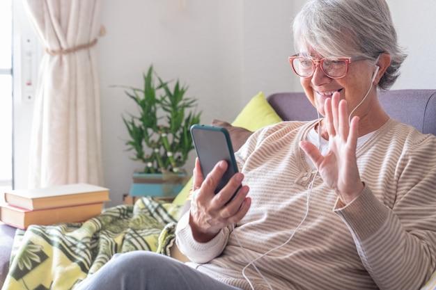 이어폰을 끼고 휴대폰으로 영상통화를 하며 집에서 소파에 앉아 웃고 있는 노부인