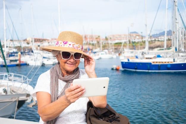 항구에 야외에 앉아 웃고 있는 노인 여성은 디지털 태블릿으로 셀카를 찍는다