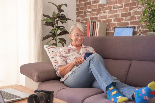Smiling senior woman sitting on sofa at home using mobile phone and laptop.