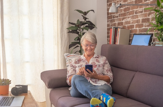 Smiling senior woman sitting on sofa at home using phone. white-haired elderly enjoying technology and retirement. bright light from window, brick wall