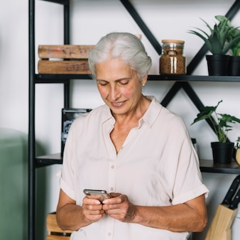 Smiling senior woman standing in front of shelf using mobile