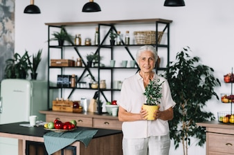 Smiling senior woman standing in kitchen holding pot plant