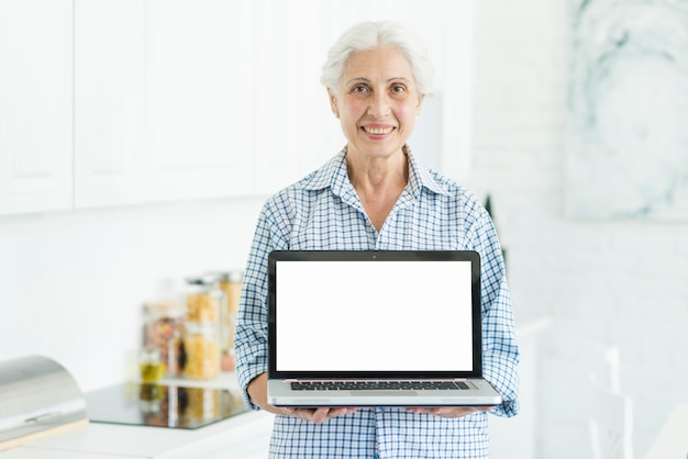 Smiling senior woman standing in kitchen showing laptop with white screen