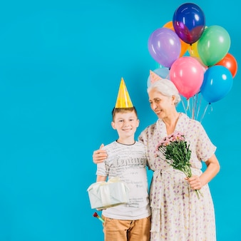 Smiling senior woman standing with grandson holding birthday gift on blue backdrop