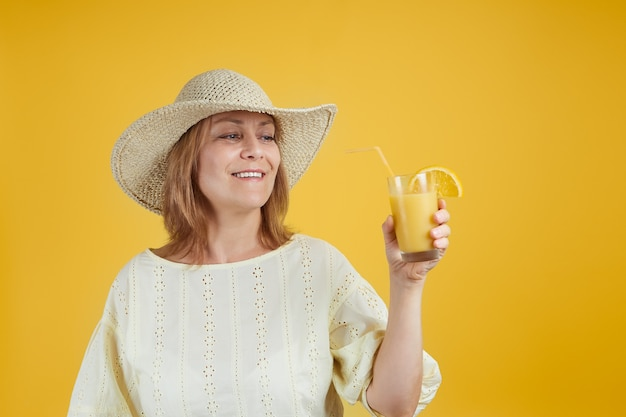 Smiling senior woman in a straw hat holding a glass of orange juice isolate on bright yellow background